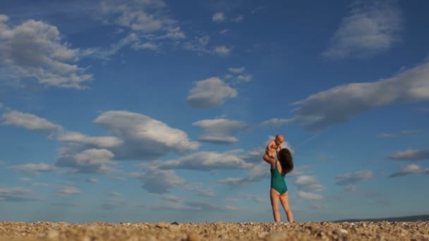 Mladá žena v zelených bikinách s dítětem na opuštěné pláži na pozadí modrého nebe a bílých mraků. Poporodní oživení, krása přírody, dovolená s dětmi