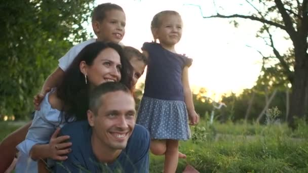 Velká rodina se třemi dětmi si hraje a baví se v trávě na venkově. Šťastná rodinná dovolená