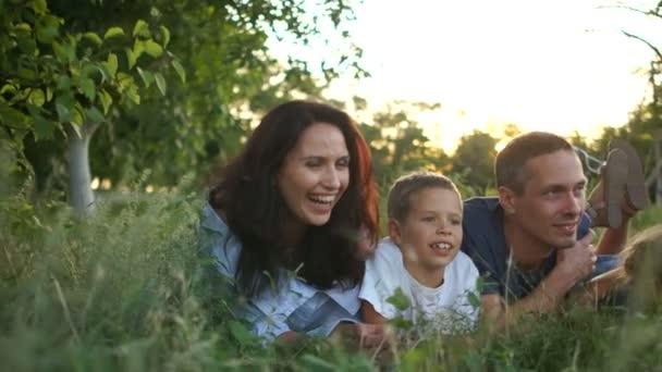 Manžel a manželka a tři děti leží v trávě při západu slunce, letních prázdninách, šťastných dětech a jejich rodičích. Krásná rodina se třemi dětmi na rodinné dovolené ve vesnici