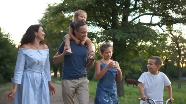 Mladý otec a matka chodí po cestě na hřišti se svými třemi dětmi. Šťastné rodinné prázdniny, letní prázdniny ve vesnici