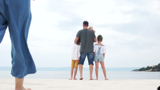 Family holidays on the Mediterranean coast. Happy family vacation. Friendly family with two children are standing on the seashore, kissing and hugging, rear view