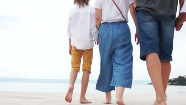 glückliche Familie verbringt das Wochenende am weißen Sand des Meeresstrandes. junge Eltern, Mann und Frau und drei Kinder. Baby in den Armen seines Vaters. Fünfköpfige Familie