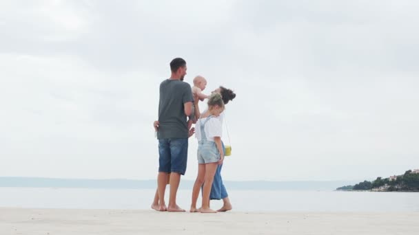 Husband and wife, lovely young couple and their three children on a white sand beach, family trip, happy family vacation