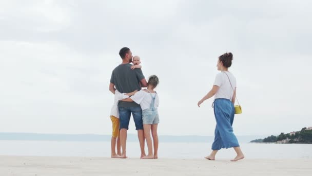 Young couple and their three children on a white sand beach, family trip, happy family vacation