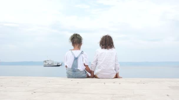 Přátelští děti sedí na molu a drží si ruce. Chlapec a dívka v letních měsících oblečené v bílých halénách. Letní prázdniny, středomořské pobřeží