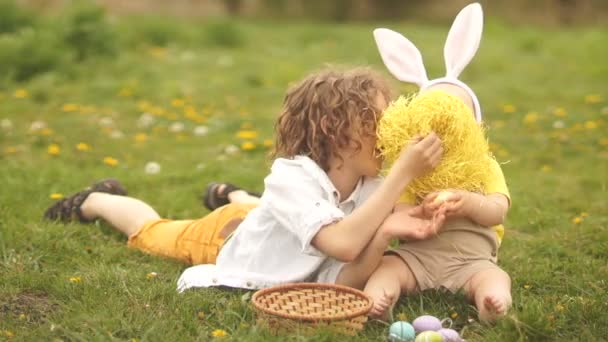 Két testvér, egy tinédzser és egy baba játszik egy húsvéti kosár. Húsvéti nyuszi jelmez, Boldog húsvéti család