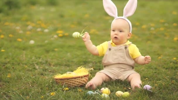 Kisgyermek egy öltöny a húsvéti nyuszi játszik húsvéti tojást ül a fűben a parkban. Tavaszi piknik, Boldog húsvéti család