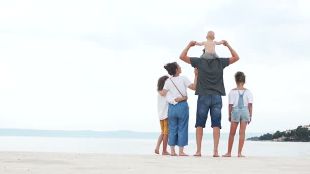 Mother and father and their three children stand on the seashore on white sand. Family dressed in jeans, happy family vacation
