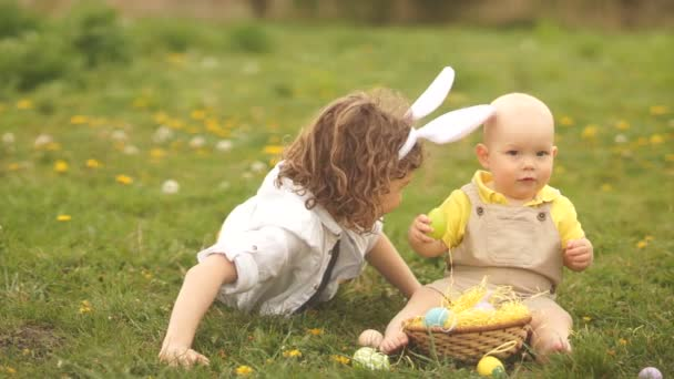 Elder and younger brother playing in the meadow with Easter baskets. Bunny ears, easter concept