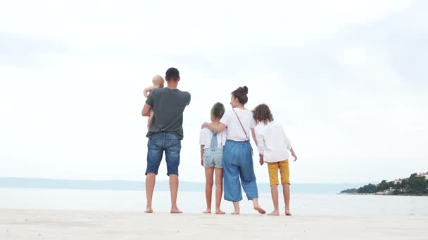 Family trip. Parents and three children dressed in jeans are resting on the white sand by the sea, summer vacation
