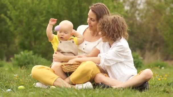 Boldog család egy pikniken a parkban. A gyerek fontolgatja a húsvéti nyuszi jelmez. Húsvét család, két testvér és anya
