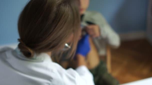 Kinderarzt Untersucht einen Schüler, hört Lunge und Herz mit einem Phonenoskop und schreibt alles in die Krankengeschichte. Internationaler Doktortag