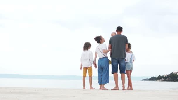 Rodiče a tři děti. Chlapec v otcově náručí natáhne ruku a legračně políbí mámu a tátu, jak otvírají pusu. Velká rodina odpočívá na pobřeží.