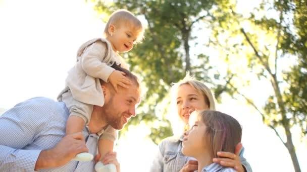 Pár dává dvě malé děti svezení na zádech s úsměvem. Šťastná rodina hraje venku. Rodina těší společně v přírodě