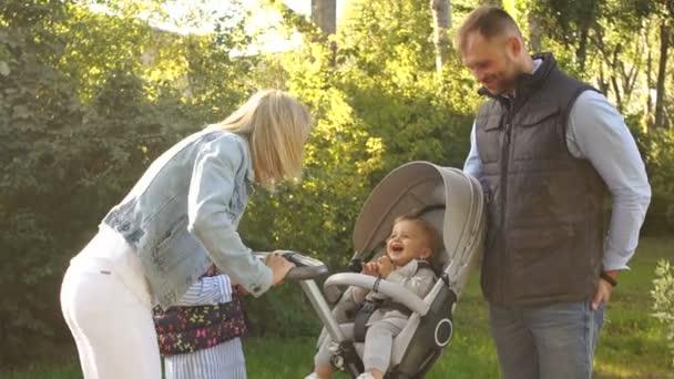 Mladá rodina na procházce v parku. Matka a otec se dvěma dívkami na procházce. Jeden rok dítě hlídání v kočárku, šťastná rodina