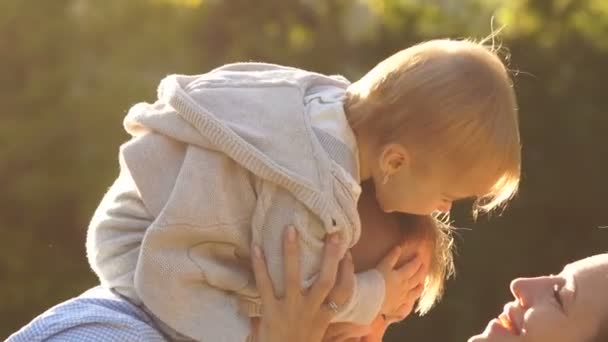One year old baby is sitting on her fathers shoulders, her mother reaches out to kiss the baby. happy family in the park for a walk