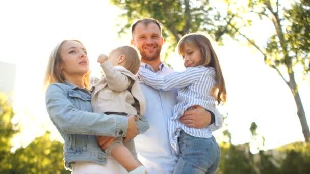 Krásná mladá rodina v parku na procházku. Čtyři lidé, matka, otec a dvě dcery na slunci