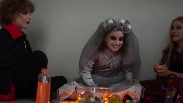 Děti slaví Halloweenskou párty. Tři teenageři jsou oblečeni v karnevalových kostýmech a s krvavým make-upem. Na stole jsou sladkosti, svíčky a dýně