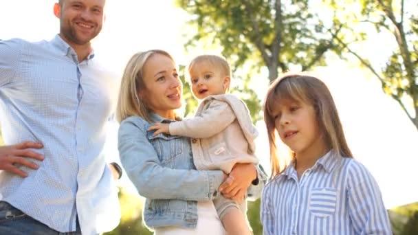 Mladá matka drží v náručí jednoleté dítě, vedle své nejstarší dcery a manžela. Šťastná rodina se dvěma dětmi na procházku v parku. Den matek