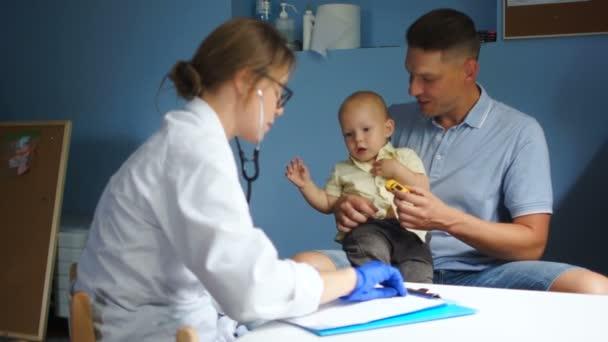 Der Kinderarzt schreibt einen Behandlungsplan in eine Krankenakte. Vater und sein kleiner Sohn vom Arzt untersucht