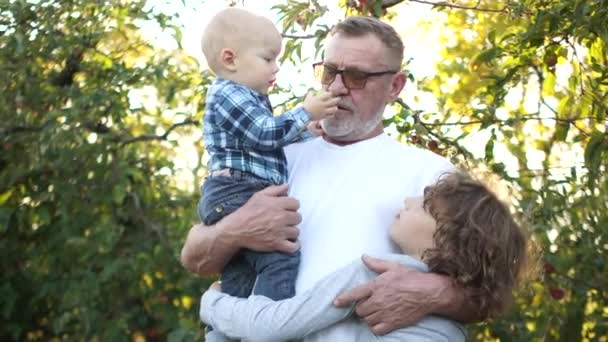 Bearded mature man with a toddler in his arms and a teenage boy hug and kiss, happy family. Grandfather and two grandchildren