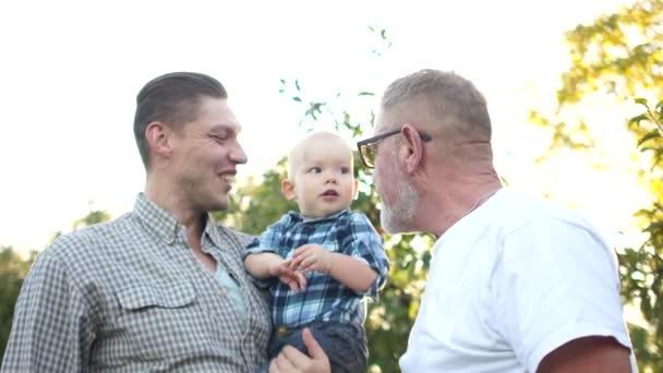 Portrét starého šedovlasého otce, jeho pohledného syna a krásného vnuka, jak se usmívají uprostřed západu slunce v parku
