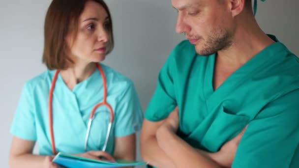 Doctors in green coats make notes in the patients medical history. Medicine and healthcare, medical staff of the clinic