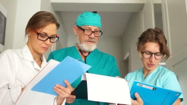 Ein älterer Mann und zwei junge Ärztinnen haben einen allgemeinen medizinischen Rat. drei Ärzte bei der Arbeit, medizinisches Personal der Klinik