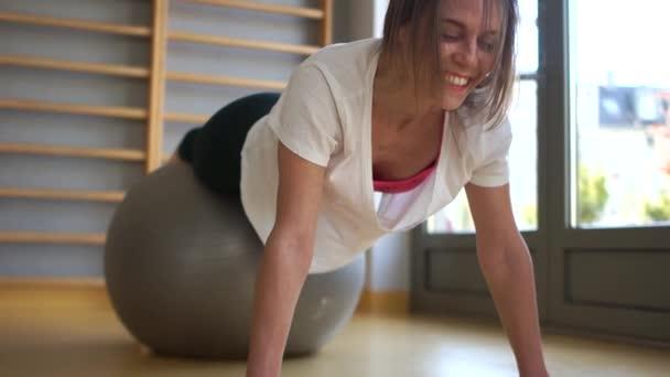 Lächelnde, fitte junge Frau, die in einem Fitnessstudio Übungen macht, die über einen Fitball balancieren. Fitness und Stretching, regelmäßiger Sport, Portrait aus nächster Nähe. Harte Arbeit im Fitnessstudio, Quarantäne-Sport