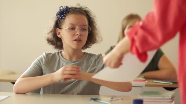 Az iskolai tanár szórólapokat osztogat a diákoknak. Utolsó vizsga az iskolában, iskolás lányok elvégzik a tesztet, a tanév végén