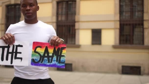 Protest proti rasismu a netoleranci. Afroameričan a běloška drží plakát, který říká, že jsme stejní a se symboly LGBT