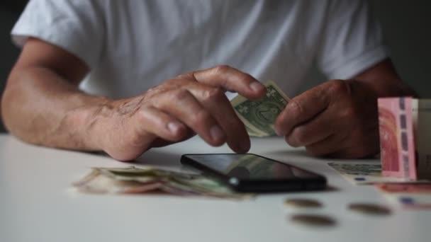 A gazdasági válság miatti megtakarításokat és a munkanélküliséget számológéppel és valutaárfolyammal rendelkező telefonnal számoló férfi jövedelembevétel csökkenése