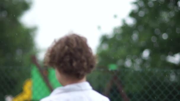Ein fröhlich gelockter Junge im weißen Hemd tanzt im strömenden Regen. Glückliche Kindheit, energiegeladener Teenager vergnügt sich im Park bei einem Regensturm