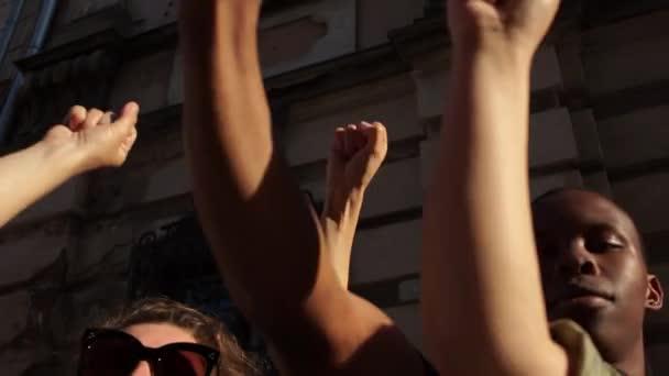 Ruce různorodých mezirasových lidí drží na pozadí městské zdi. Černý muž a ženské ruce. Black Lives Matter. Antiracismus. Rovnost.