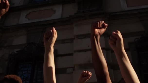 Zaťaté pěsti vztyčené ve vzduchu. Násilné protesty, na černých životech záleží, lidé skandují zastavit rasismus slogany, různé skupiny lidí
