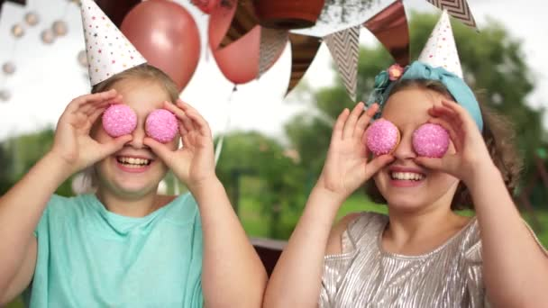 The birthday girl and her friend have fun eating pink cakes at her birthday party. Catering concept, childrens birthday outdoor