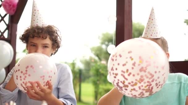 Happy kids inflate balloons for birthday party. Boy and girl in birthday hats inflate balloons with sequins and have fun