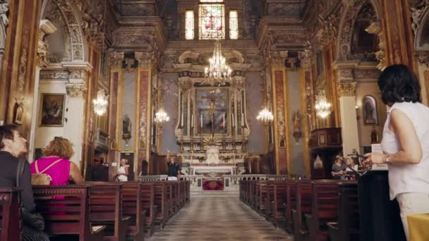NICE, FRANCE - JULY 2018: Famous Church of Gesu view from the inside. Camera showing beautiful richly decorated interior with altar, benches and people sitting and moving around in slow-motion.