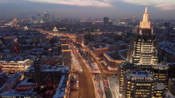 Aerial shooting of Moscow Garden Ring in the evening. City lights in the dusk. Business center Armory tower at sunset.