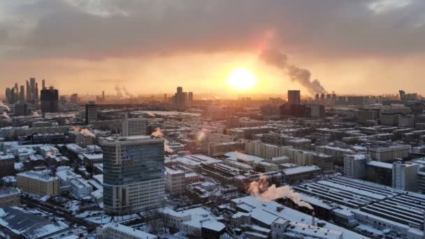 Aerial Moscow winter view, sunset city skyline timelapse, cold russian cityscape scene, sun shining through cloudy evening sky.