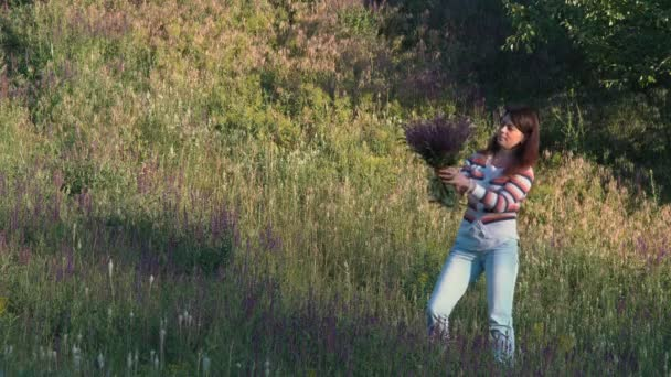 Beautiful Woman Looks at a Bouquet of Just Torn Field Flowers in the Woods