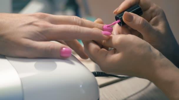 Detail, mistr manikúra: použití růžový lak na nehty na Zenske ruky
