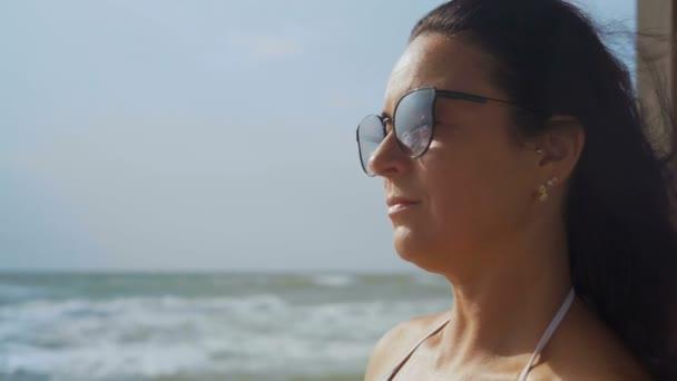 Detail, krásná žena v bílé plavky a sluneční brýle pije koktejl sedící na břehu moře