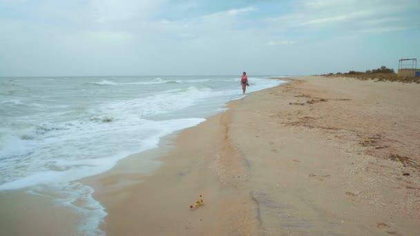 Krásná žena chůze naboso moře na pláži v větrného počasí