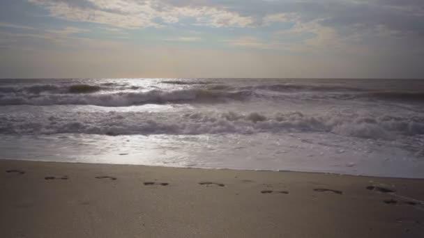 Hullámok a tenger reggel mossa lábnyomok a homok