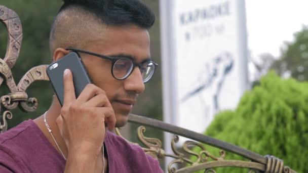 Close-up indischen Kerl in Brille spricht am Telefon sitzen auf einer Bank im Park