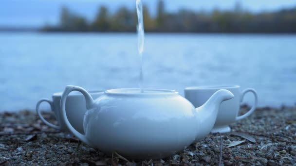 Close-up, a jet of boiling water pouring into a white porcelain teapot standing on a stony river bank