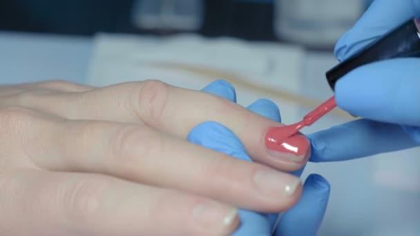 Makro-, Maniküre-Meister verteilt rote Lackschicht auf Fingernägel von Frauen