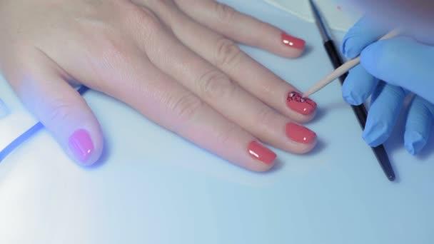 Nahaufnahme, Meister Maniküre verziert den Nagel auf der Hand der Mädchen mit künstlichen facettierten Kieselsteinen
