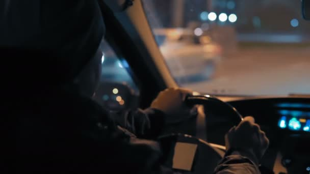 Close-Up, Rear View of a Man Driving a Car Driving through the Night City